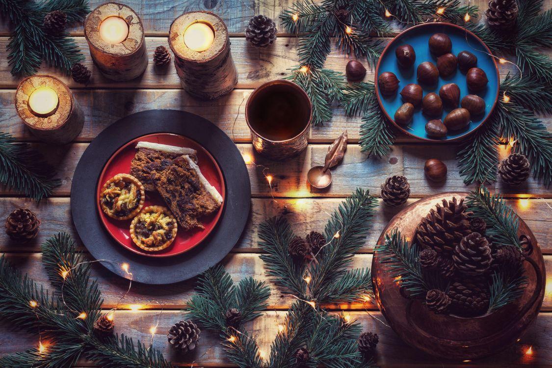 Фото бесплатно натюрморт, Свечи, Зелень, Праздничный стол, Каштаны, пироги, шишки, Рождество, праздники
