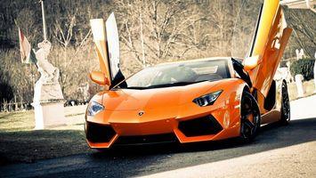 Фото бесплатно ламборджини, спорткар, оранжевый, двери вверх, фары, диски