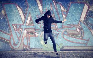 Бесплатные фото парень,толстовка,капюшон,джинсы,кроссовки,танец,стена