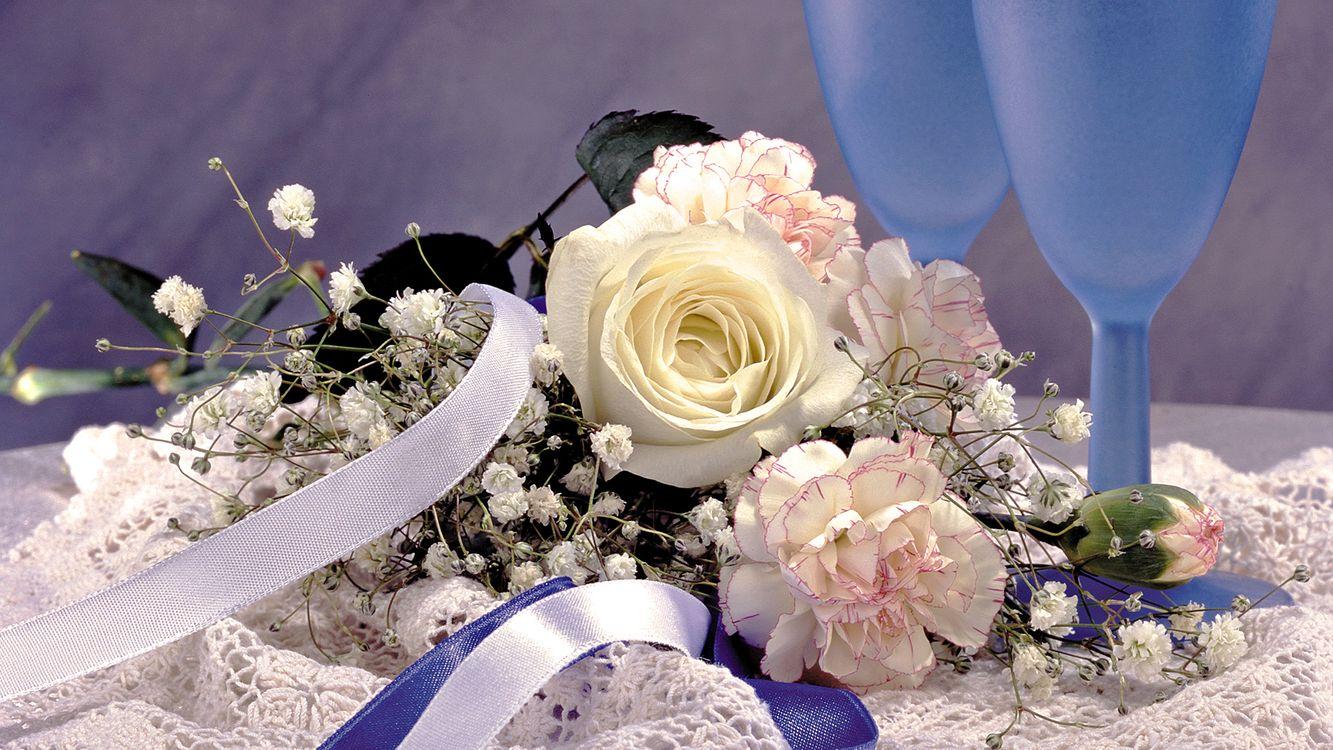 Фото бесплатно гвоздики, розы, листья, стебель, шипы, ленточка, букет, бутон, салфетка, скатерть, бокалы, фужеры, голубые, фон, серый, цветы