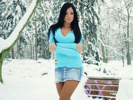 Обои девушка, брюнетка, светер, джинсовая, юбка, зима, улица, скамейка, снег, лес, елки, позирует