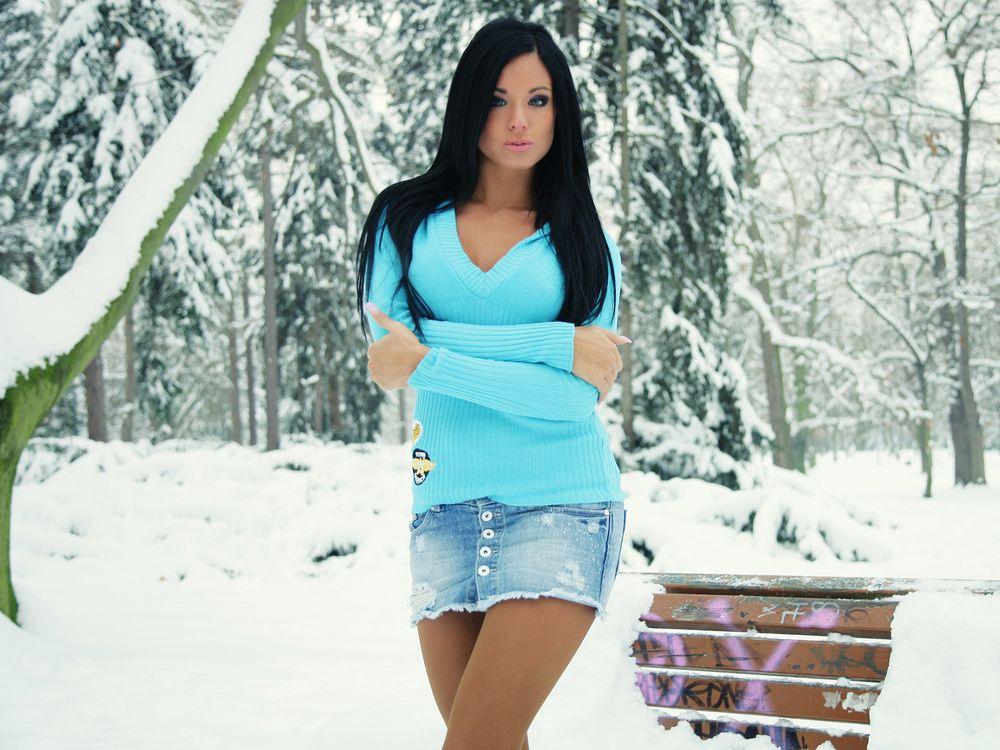 Фото бесплатно девушка, брюнетка, светер, джинсовая, юбка, зима, улица, скамейка, снег, лес, елки, позирует, фото, красавица, глазки, девушки