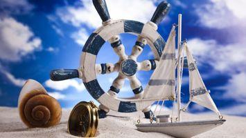 Обои штурвал, корабль, песок, небо, облака, мель, компас, ракушка, паруса, пейзажи
