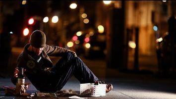 Обои парень, обочина, бутылка, вино, асфальт, тротуар, пить, шапка, куртка, вечер, журнал, огни