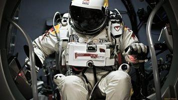 Фото бесплатно космонавт, скафандр, сидит, приборы, руки, перчатки, космос