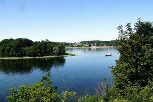 Обои река, вода, деревья, трава, кусты, город, дома, здания, катер, яхта, остров, пейзажи