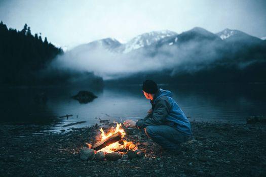 Photo free man, bonfire, river bank