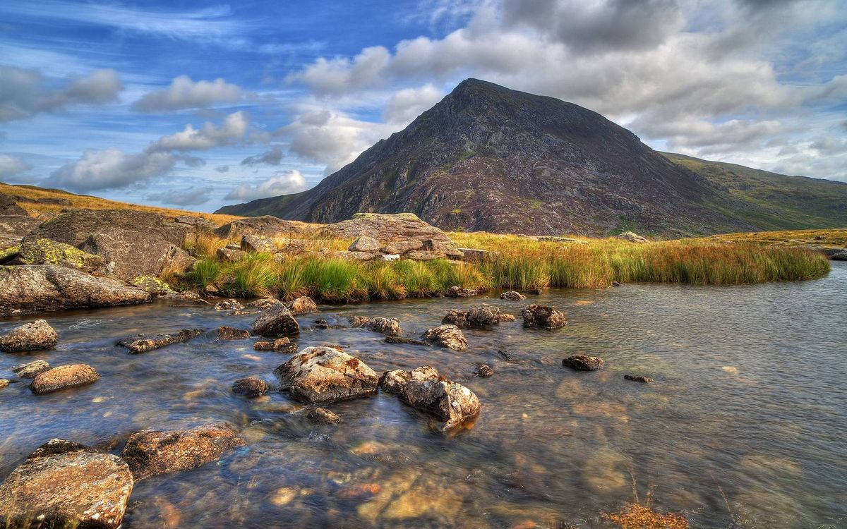 Фото бесплатно река, камни, берег, трава, гора, небо, облака, природа