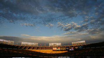 Бесплатные фото стадион,фонари,небо,облака,солнце,трибуны,флаги