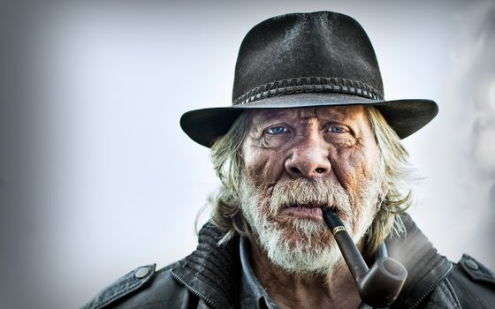 Photo free portrait of an old man, a pipe, a beard