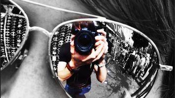 Обои очки, отражение, солнцезащитные, фотограф, фотоаппарат, люди, толпа, волосы, часы, браслет, улица, тротуар