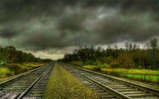 Обои рельсы, шпалы, железная, дорога, камни, кусты, деревья, осень, небо, тучи, природа