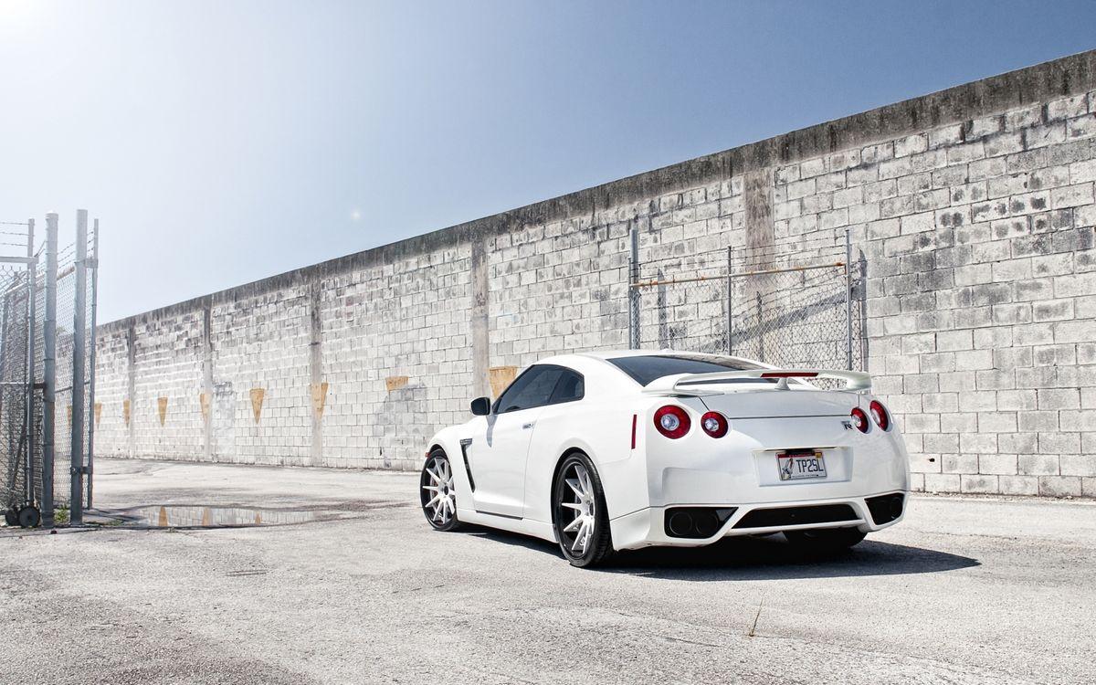 Фото бесплатно автомобиль, gt-r, белый, фары, колеса, кузов, труба, кирпич, забор, стена, лужа, дорога, асфальт, машины, машины