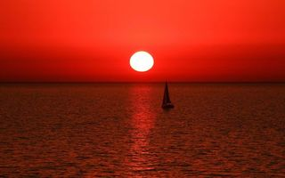 Photo free sailboat at sunset, red sky, ripples