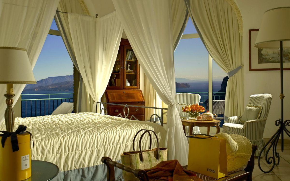 Фото бесплатно спальня, кровать, занавески, светильники, старинный стиль, картина, столик, сумочка, кресло, окна, вид на море, остров, интерьер