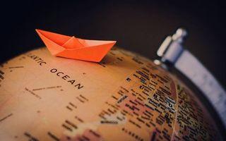 Фото бесплатно глобус, карта, кораблик бумажный, фон черный