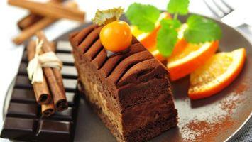 Бесплатные фото тарелка,пирожное,шоколад,палочки корицы,дольки апельсина,листья зеленые