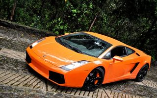 Фото бесплатно ламборджини, спорткар, оранжевый, фары, диски, брусчатка, кустарник