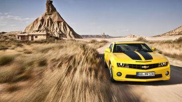 Фото бесплатно шевроле камаро, спорткар, желтый, дорога, скорость, строение, гора