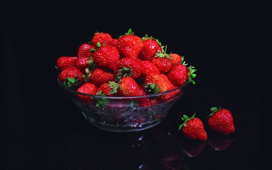 Photo free strawberries in the dish, transparent plate, black background